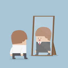 Businessman see his successful future in the mirror