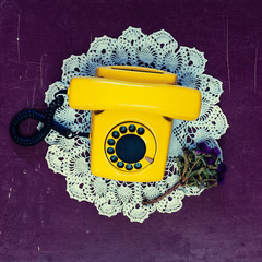 Yellow vintage telephone old wooden background