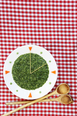 Food clock - plate with creamed spinach and spaghetti,