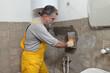 Home renovation, mason fixing mortar at wall with trowel