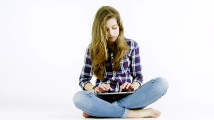 Blond teenager girl with long hair writing with tablet