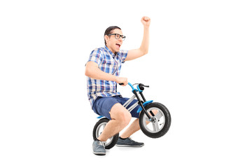 Crazy young man riding a small bike