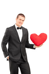 Elegant guy holding a red heart shaped pillow