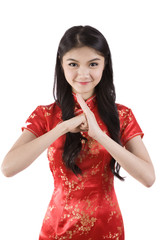 Chinese girl in traditional Chinese cheongsam greeting, isolated