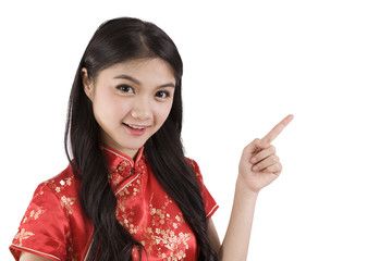 Chinese girl in traditional Chinese cheongsam pointing at blank