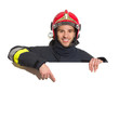 Smiling fireman in red helmet pointing at the blank banner - 75449127