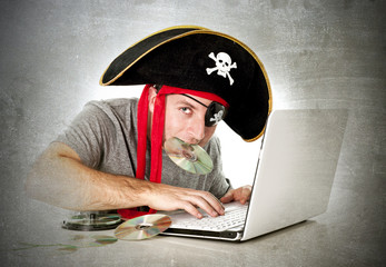 man in pirate hat downloading music files and movies on computer