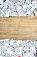 Shredded newspaper pieces on wooden surface.