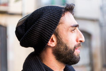 Portrait of trendy guy wearing hat in the city at winter