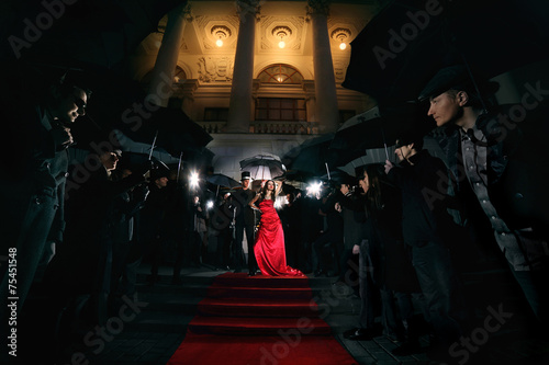 Leinwanddruck Bild woman in red dress on the red carpet photos of paparazzi