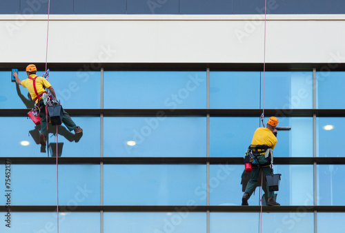 Leinwanddruck Bild Two workers washing windows of the modern building
