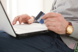 Closeup of senior male hands with credit card and laptop