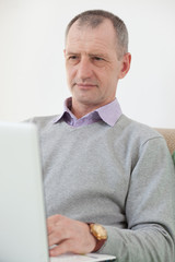 Adult man using a laptop at home