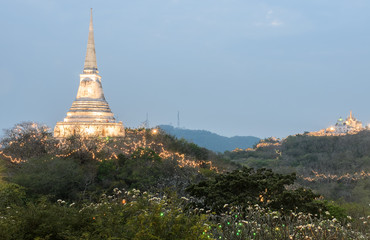 White pagoda illuminated on hill at sunset