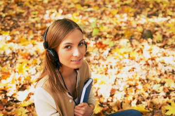 Student sitting with headphones among maple leaves and looking u