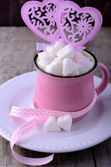 Pink ceramic mug on the wooden background full of sweet hearts