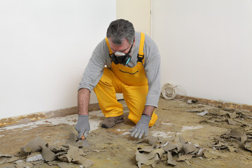 Worker with mask cleaning floor with putty knife, renovation