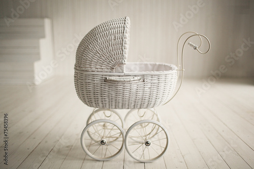 Beautiful old fashioned white pram in white room