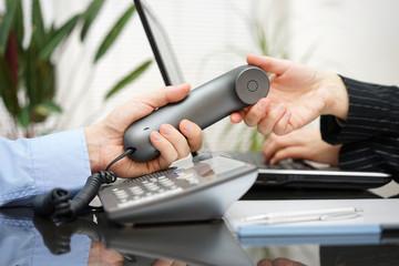 Businessman  gives woman handset. teamwork and customer support