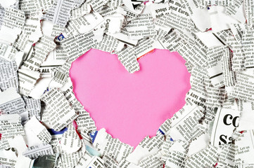 Pink heart shape and shredded newspaper pieces.