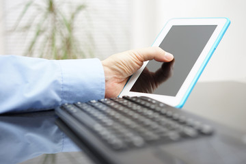 male is working on tablet and personal computer