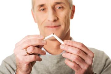 Portrait of mature man breaking cigarette