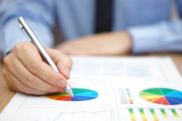 Businessman is analyzing business report with charts and diagram
