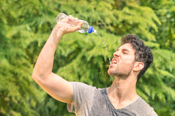 Sporty man refreshing with cold water after run training