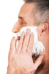 Side view of a man applying shaving foam