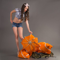 brunette in style pinup stands near jellyfish of parachute