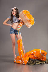 girl in style pinup holds orange jellyfish of parachute