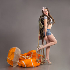 flighty girl in style pinup stands near jellyfish of parachute