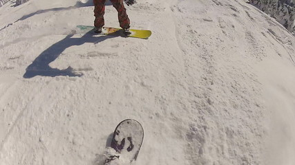 Two snowboarders crash into each other while riding