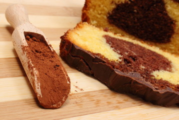 Powdery cocoa on wooden spoon and chocolate cake