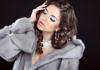Glamour fashion beautiful woman wearing in luxurious fur coat is