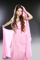 Beautiful young woman in pink chiffon dress. Makeup. Long wavy h