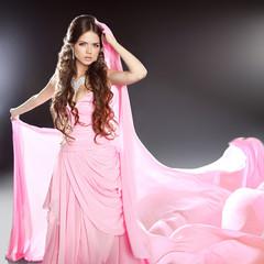 Beautiful brunette girl model in blowing transparent chiffon dre