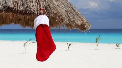 Christmas sock on sun umbrella at caribbean beach. Holiday conce