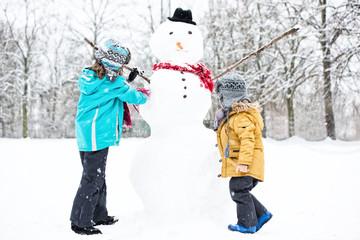 Kinder bauen Schneemann im Winter