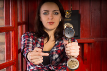 Woman pointing to a vintage telephone handset