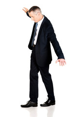 Full length businessman walking carefully
