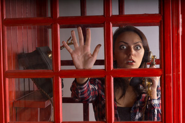Terrified woman trapped in a telephone booth