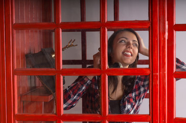 Happy young woman chatting on a public phone