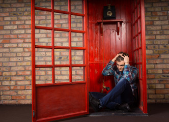 Troubled Man Sitting on Floor of Telephone Booth