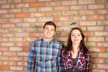 Smiling Couple Standing in front of Brick Wall