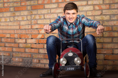 Poster Young Man Riding on Vintage Toy Car
