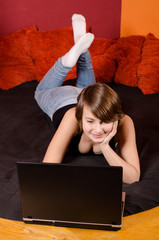 Happy teenage girl having fun with notebook at home