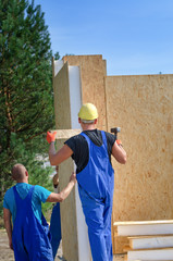 Two builders installing a wooden wall panel