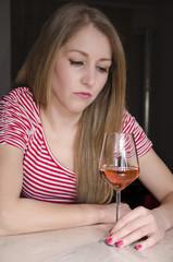 Sad depressed cute girl drinking alone.