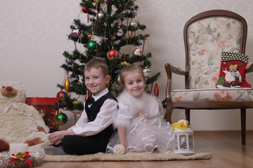 Girl and boy sittting Christmas tree